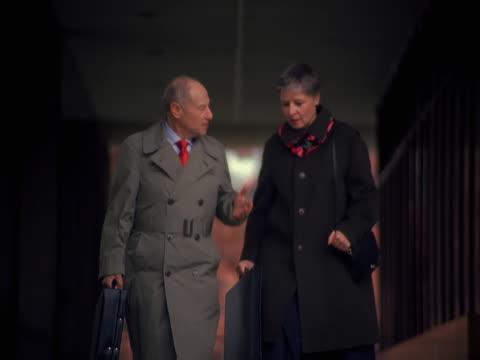stockvideo's en b-roll-footage met businessman and woman walking together - compleet pak