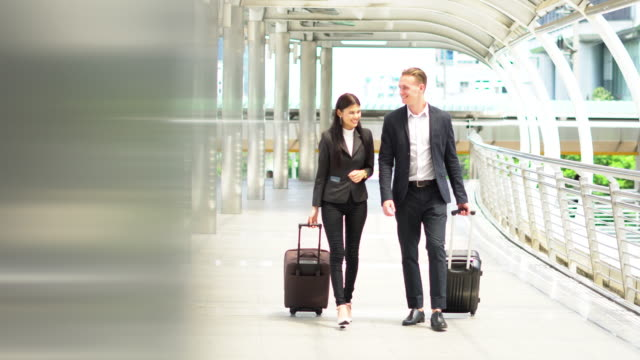 Businessman and woman walking with suitcase go to working