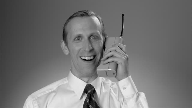B/W CU Businessman answering large  early mobile phone and having animated conversation/ New York City