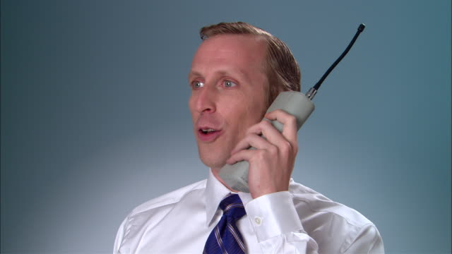 cu businessman answering large, early mobile phone and having conversation/ new york city - 2000s style点の映像素材/bロール