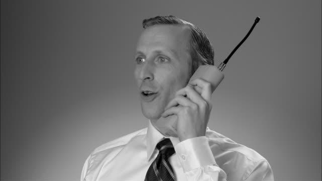 b/w cu businessman answering large  early mobile phone and having conversation/ new york city - sladdlös telefon bildbanksvideor och videomaterial från bakom kulisserna