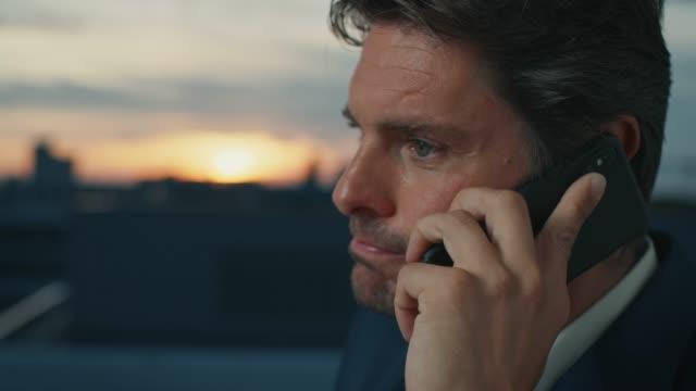 stockvideo's en b-roll-footage met zakenman die telefoon beantwoordt in stad bij zonsondergang - opluchting