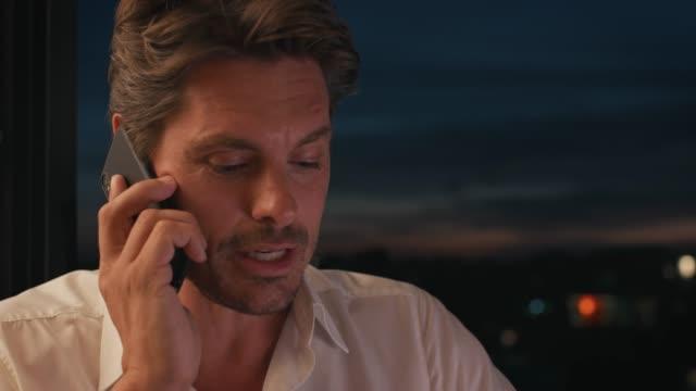 Businessman answering smart phone at sunset