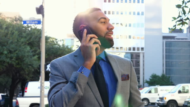 vidéos et rushes de ms businessman answering smartphone while standing on city sidewalk during early morning commute - chemise et cravate