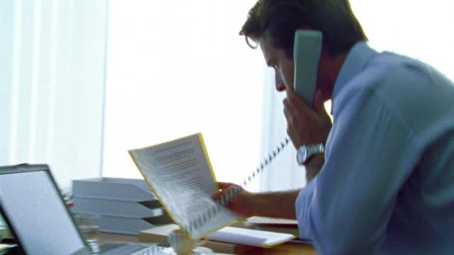 vídeos de stock e filmes b-roll de businessman answering telephone + sitting down at desk reading document - sentar se
