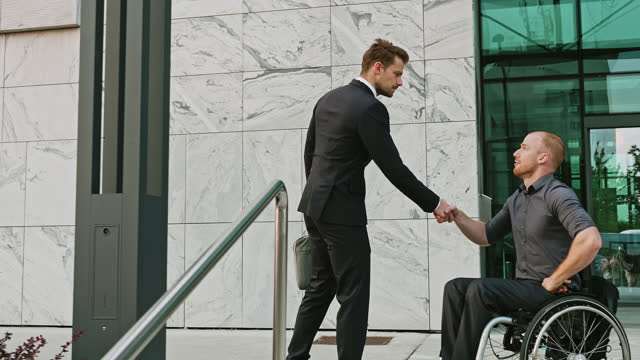 businessman approaching disable businessman on wheelchair and shaking hands outdoors - mid adult men stock videos & royalty-free footage