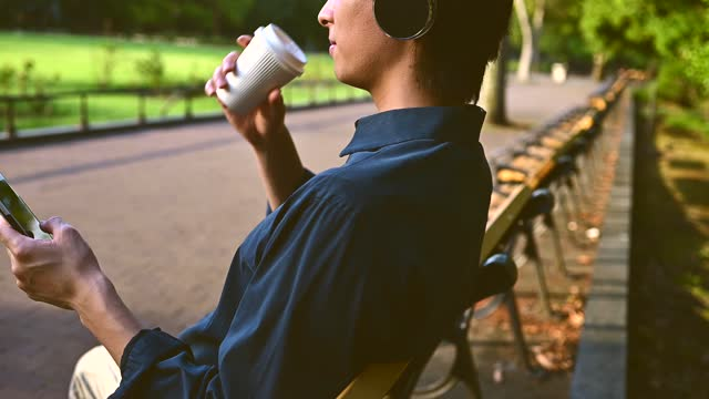 a businessman are taking a break with coffee at public park - bluetooth stock videos & royalty-free footage