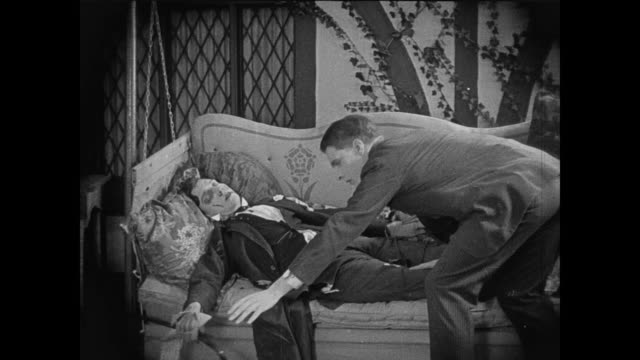 1920 businessman (buster keaton) arrives home exhausted; his servant helps him lay down - müde stock-videos und b-roll-filmmaterial