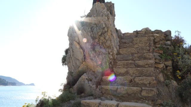 Businessman ascends stone steps above sea