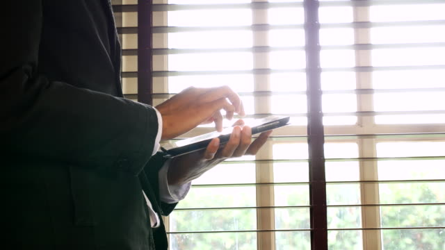 Businessman at a window scrolling through his tablet. Close up