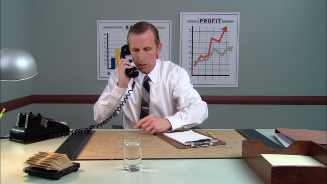 ms businessman at desk, dialing on rotary phone/ hand giving man mobile phone/ man talking on mobile phone, scrutinizing it, then smiling and talking to camera/ new york city - rotary phone stock videos and b-roll footage