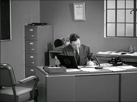 vidéos et rushes de b/w 1951 businessman at desk doing paperwork / stands up as colleague enters room + hands him paper - rapport