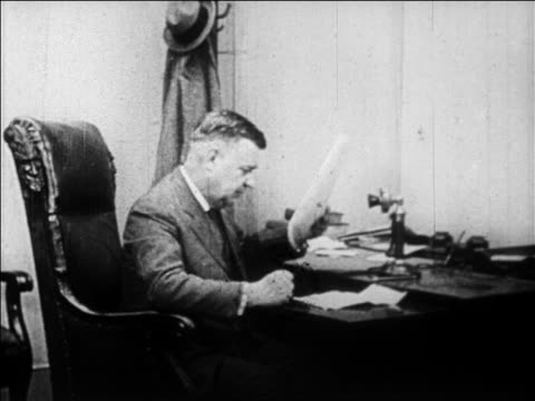 b/w 1929 businessman at desk in office looking at newspaper picking up telephone / newsreel - one mature man only stock videos & royalty-free footage