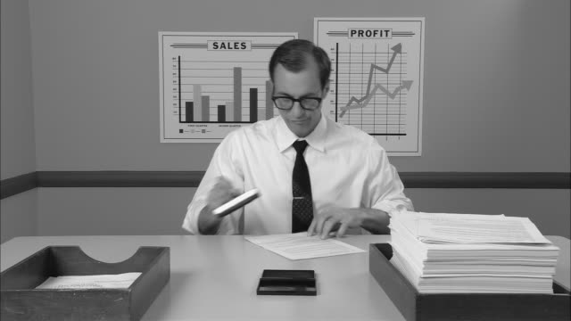 b/w ms businessman at desk stamping stack of papers  moving them from inbox to outbox/ new york city - boredom stock videos & royalty-free footage