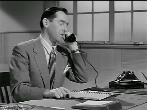vídeos de stock e filmes b-roll de b/w 1954 businessman at desk talks on phone, hangs up, writes in appointment book then walks away - 1954