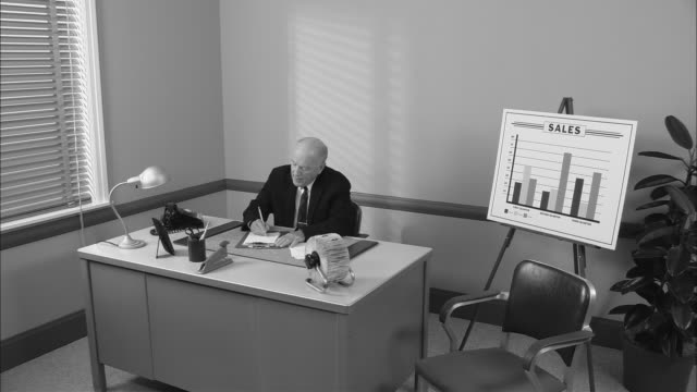 B/W MS Businessman at desk writing on notepad/ Secretary arriving and giving him a file and cup of coffee before sitting down and taking notes as he talks/ New York City
