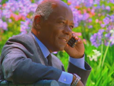 vidéos et rushes de businessman at park talking on mobile phone - calvitie