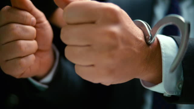 slo mo ld businessman being handcuffed - manette video stock e b–roll