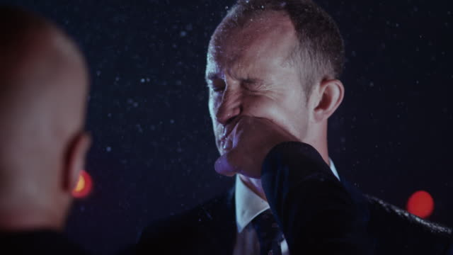slo mo ld businessman being hit in the face in rain - punching stock videos & royalty-free footage