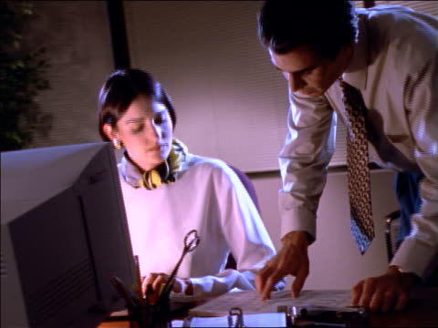 vídeos y material grabado en eventos de stock de businessman brings paper to woman at desk, they talk - 1990
