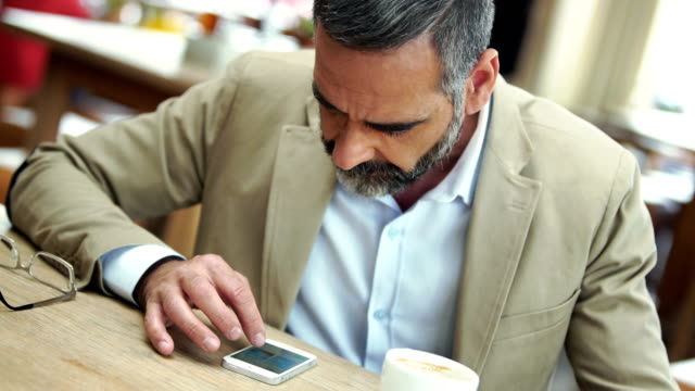 businessman browsing web on his smart phone. - mature men stock videos & royalty-free footage