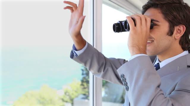 stockvideo's en b-roll-footage met businessman businessman looking through binoculars while waving - verrekijker