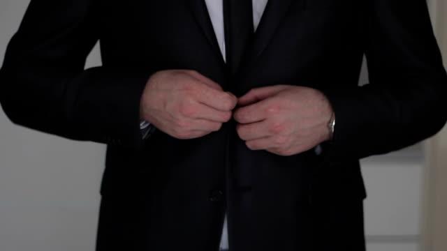 stockvideo's en b-roll-footage met businessman buttoning  to suit - bijstellen