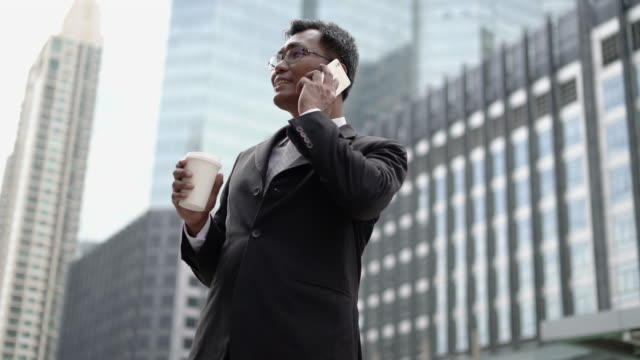 vidéos et rushes de téléphone d'affaires ont une bonne nouvelle et repartir. - east asian ethnicity