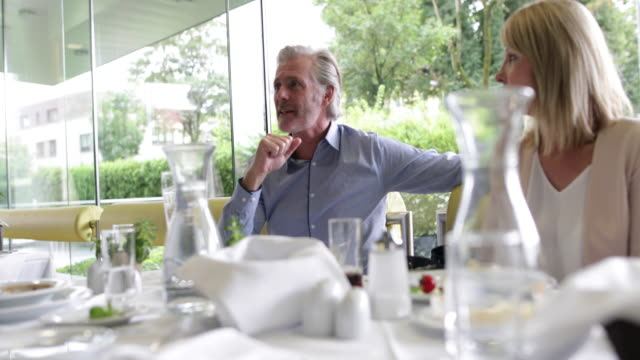 Businessman calling waiter to table