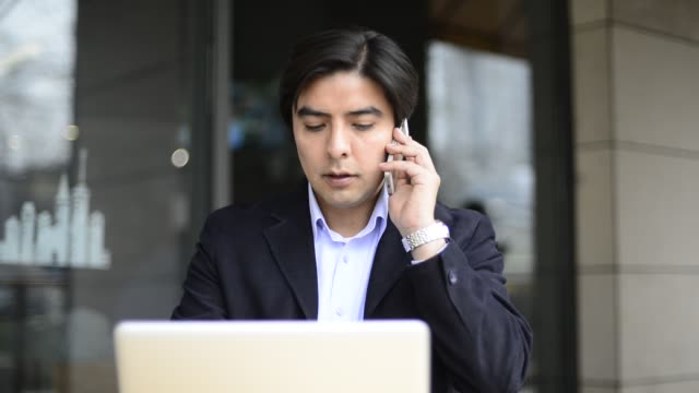 businessman calling while using laptop outside cafe