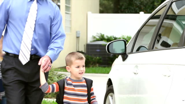 businessman carrying baby taking boys to school - busy morning stock videos & royalty-free footage