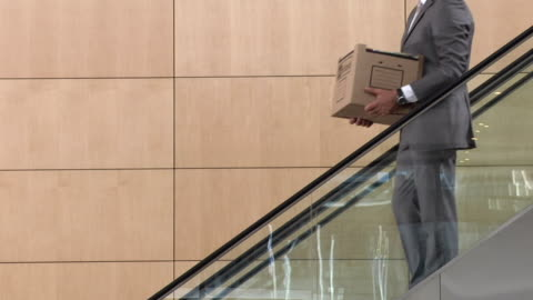 stockvideo's en b-roll-footage met slo mo ms businessman carrying box of office items moving down escalator, young man moving up, cape town, south africa - werkloosheid