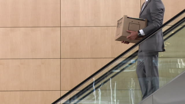 vídeos de stock e filmes b-roll de slo mo ms businessman carrying box of office items moving down escalator, young man moving up, cape town, south africa - desemprego