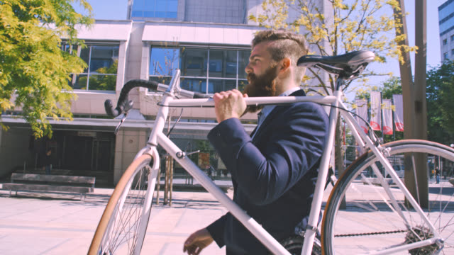 ms businessman carrying his bicycle down the street - hipster person stock videos & royalty-free footage