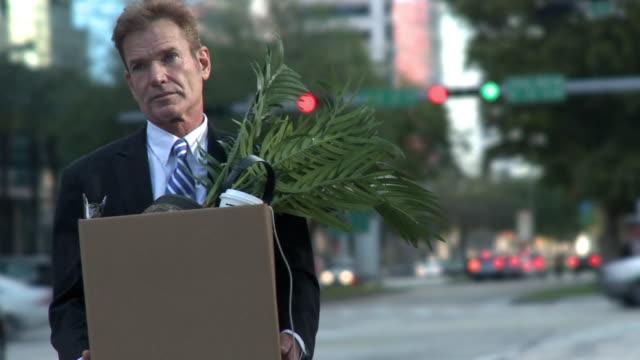 MS Businessman carrying office belongings / South Beach, Florida, USA