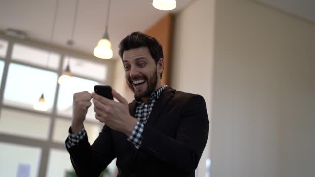 vídeos de stock, filmes e b-roll de empresário comemora boas notícias no celular - loteria