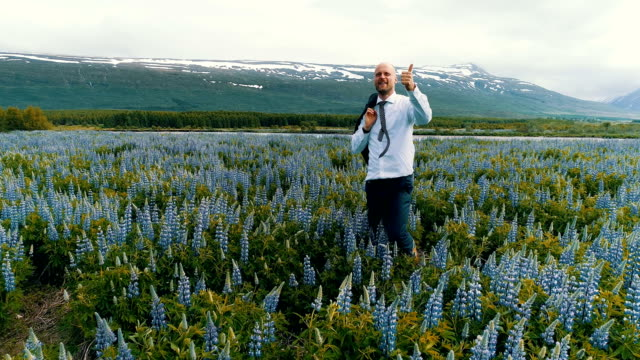 Businessman celebrating success on a meadow full of flowers