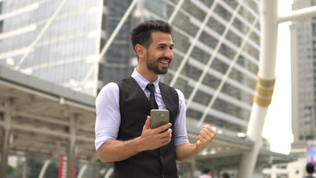 Businessman Celebrating Victory Looking at smartphone