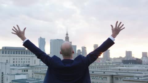 affärsman fest framgång på taket. - framgång bildbanksvideor och videomaterial från bakom kulisserna