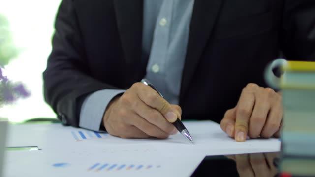 vidéos et rushes de homme d'affaires de vérifier et d'analyser le papier millimétré pour son travail au bureau, dolly tourné de gauche à droite - investissement