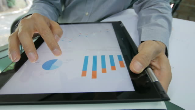 businessman checking and analyzing graph on digital tablet , dolly shot right to left - big data video stock e b–roll