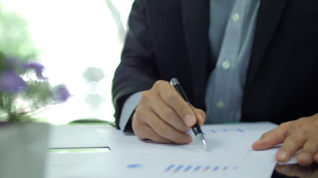 vídeos de stock e filmes b-roll de businessman checking and analyzing graph on working space at office - negociante ocupação financeira