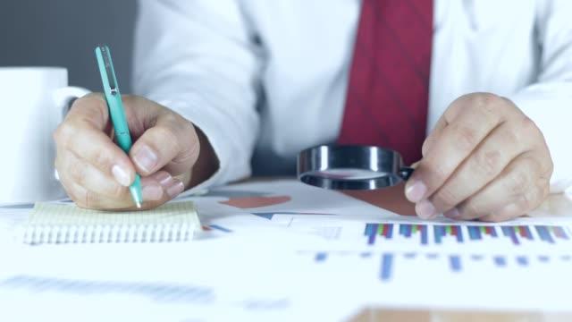 vídeos de stock e filmes b-roll de businessman checking financial reports on table - lupa equipamento ótico
