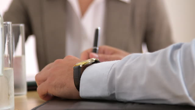 Businessman checking his watch in a meeting