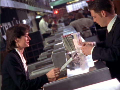 CANTED businessman checking in at ticket counter of airport / female ticket agent