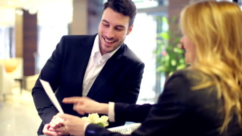 businessman checking in to a hotel - receptionist stock videos & royalty-free footage