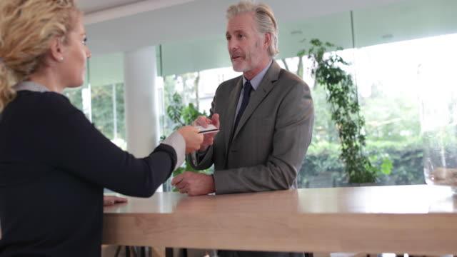 vídeos de stock, filmes e b-roll de businessman checking into a hotel - recepcionista