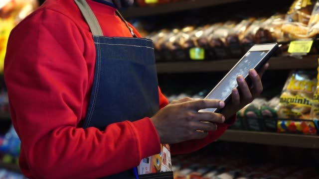 businessman checking inventory in a digital tablet at a supermarket - manager stock videos & royalty-free footage