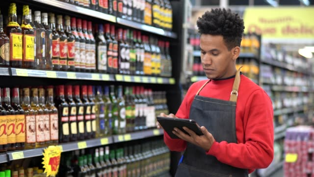 businessman checking inventory in a digital tablet at a supermarket - filmato non girato negli usa video stock e b–roll