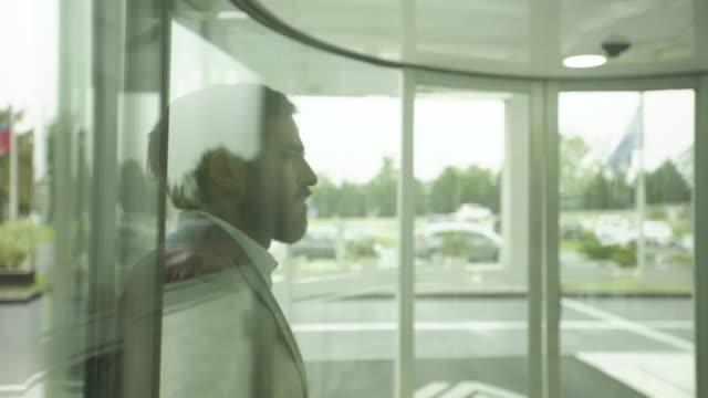 businessman checking smartphone in lobby and looking upset - spegling bildbanksvideor och videomaterial från bakom kulisserna